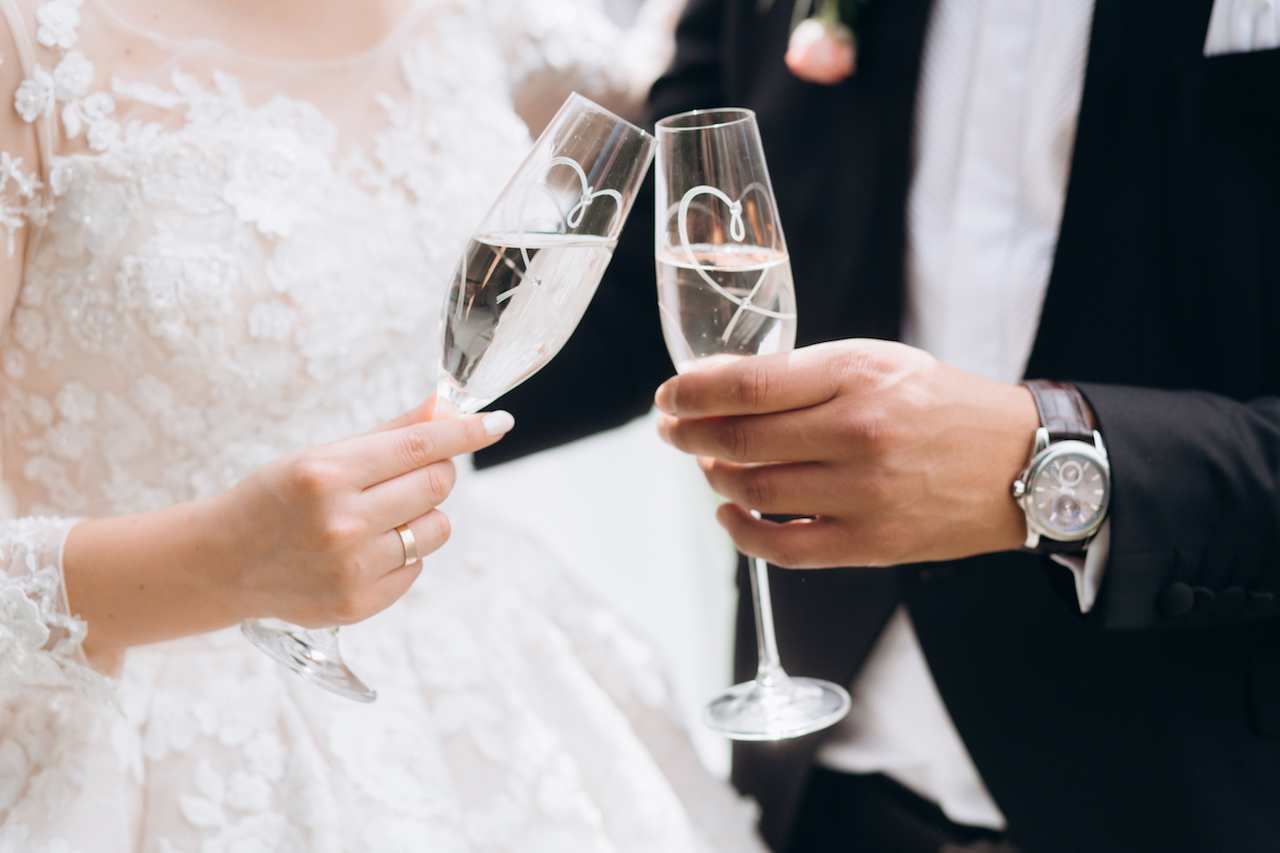Groom with bride are knocking glasses with champagne
